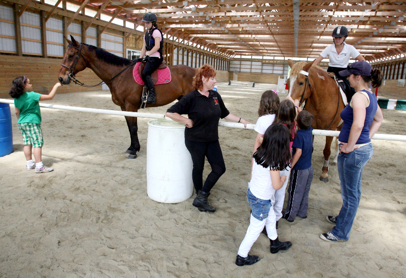 Anne Luke, owner of Holly Ridge Farm Equestrian Center near Willards, MD, center, introduces some lesson horses and instructors to visitors of the facilities 2010 open house.